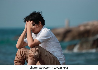 Anxious depressed Asian man covering face with hands and bend down head