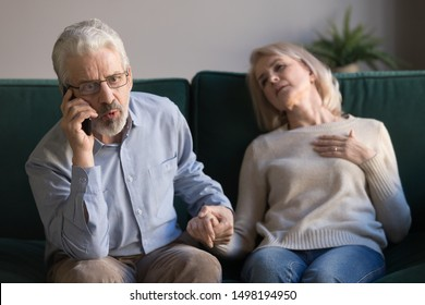 Anxious elderly husband hold wife hand call talk with emergency, ask help for woman having heart attack, worried mature male speak with 911 saving sick senior spouse suffering from coronary disease