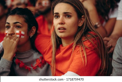 Anxious England team supporter watching a live match from stadium. English soccer fans in crowd looking upset during game.