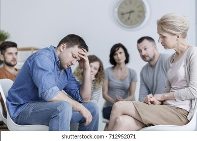 Anxious man holding his head during conversation in support group in room with clock