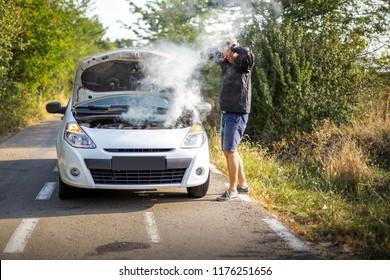 An anxious man near a broken car on the road