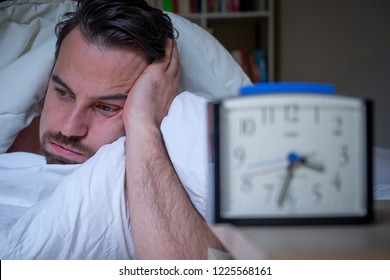 Anxious man suffering insomnia watching alarm clock