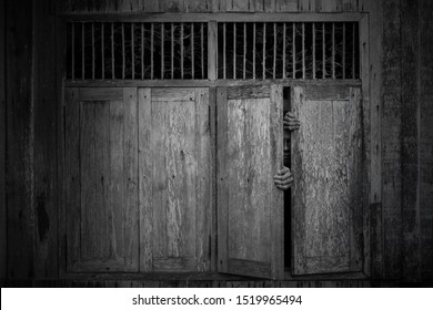 Anxious and scared man opened old wooden windows ajar and peeping through from behind in the dark, Scary monochrome background
