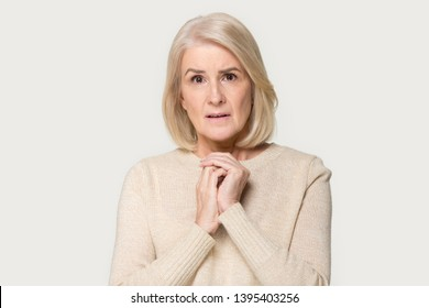 Anxious senior blond woman folded hands together looks at camera pose isolated on grey background, mature female feels desperate or frightened, concept of age specific psychological physical changes
