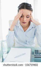 Anxious stylish brunette businesswoman holding her head in bright office