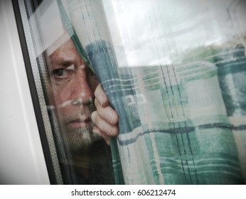 Anxious or suspicious man peeping through window from behind curtain - mental health concept.