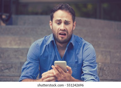 Anxious upset young scared man looking at phone seeing bad news or text message sitting on stairs outside corporate building. Human emotion, reaction, expression