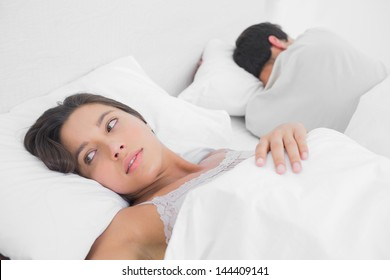 Anxious woman sleeping in bed next to her partner