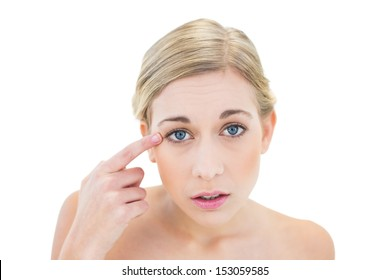 Anxious young blonde woman pointing her eye with her finger on white background