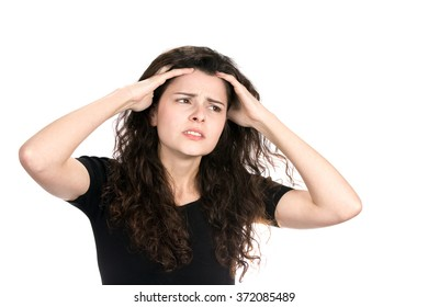 Anxious young businesswoman runs her fingers through her hair as she worries and stresses about her situation.