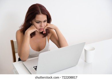 Anxious young businesswoman sitting at laptop