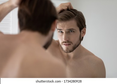 Anxious young Caucasian man look in mirror in bathroom touch check head worried about dandruff, concerned millennial male frustrated about hair loss, receding hairline, haircare, beauty concept - Shutterstock ID 1734280928