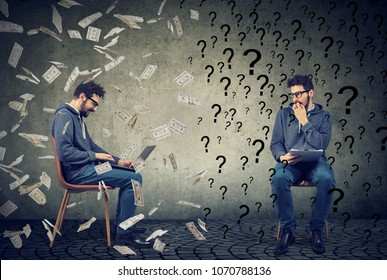 Anxious young man with many questions looking at successful smart guy working on laptop computer under money rain