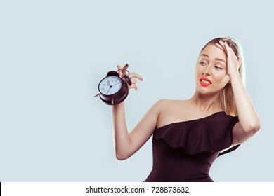 Anxious young woman looking at alarm clock. Time pressure concept. Human emotions face expression