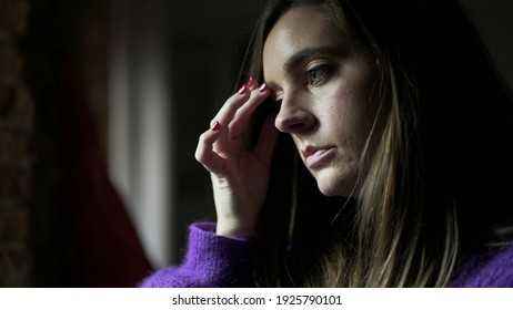 Anxious young woman standing by window concerned with life problems