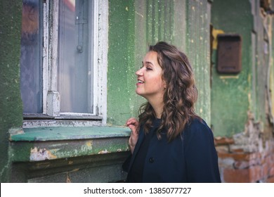 Is anybody home ? Curious woman looking through window to old house in city. Voyeurism concept