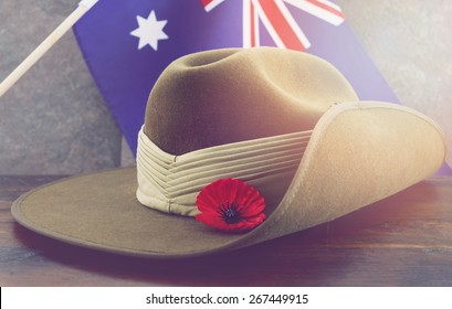 Anzac army slouch hat with Australian Flag on vintage wood background with applied retro vintage filters and added light effects.