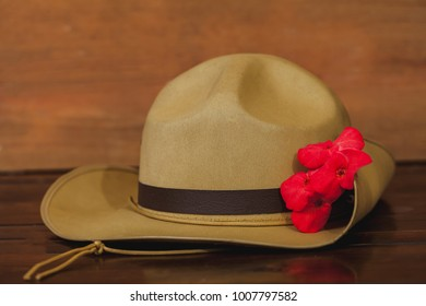 Anzac army slouch hat with red flower on vintage wood   background .