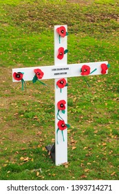 """Anzac (Remembrance) Day Cross Decorated With Red Poppies. The Message on it Reads """"A New Zealand Soldier, Known Unto God"""""""