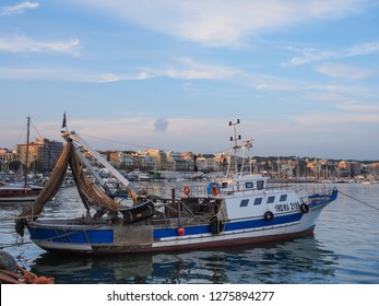 Anzio / Italy - 10 20 2018: View of Anzio town with small fishing trawler boat at the front and harbour of various ships and yachts during sunset. Metropolitan City of Rome, Lazio region of Italy.