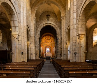 Anzy-le-Duc, France - August 1, 2018: Interior Historical romanesque church of Anzy le Duc with wooden benches and high pilars with capitals, Saonne-et-Loire, France.