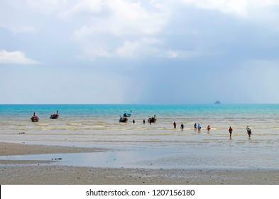 Ao Nang, Thailand - April 23, 2017: Tourists leaving a long tail boat at Nopparat Thar beach at low tide.