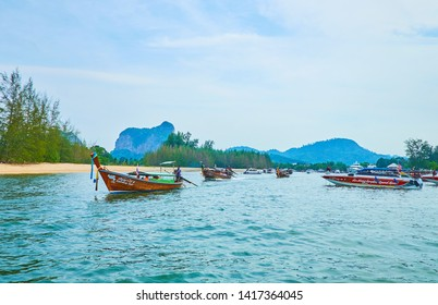 AO NANG, THAILAND - APRIL 27, 2019: The longtail and speed boats float along the Klong Son canal to Andaman sea, on April 27 in Ao Nang