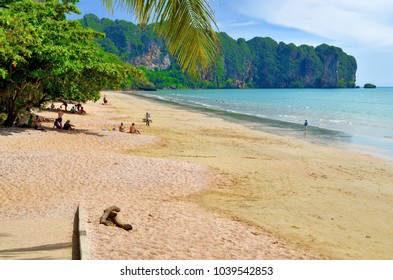 Ao Nang, Thailand - October 18, 2013. Southern part of Ao Nang beach at low tide with people sitting under the trees.