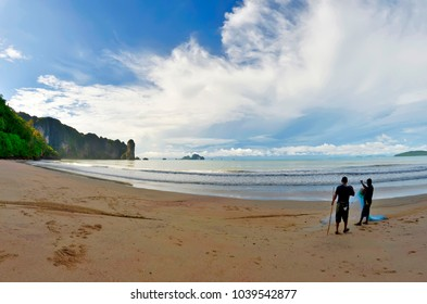 Ao Nang, Thailand - October 21, 2013. Two fishermen on the beach early in the morning, with Poda island in the background.
