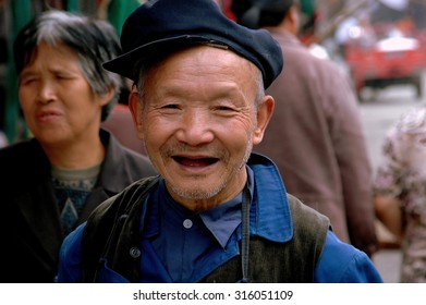 Ao Ping, China - September 14, 2006:  Smiling, elderly, toothless, Chinese man wearing a cap