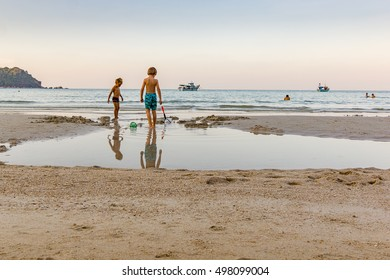 Ao Thong Nai Pan Yai, Koh Pangan, Thailand, April 22, 2016, Two little boys play with water and buckets in the sand on a beach in Thailand