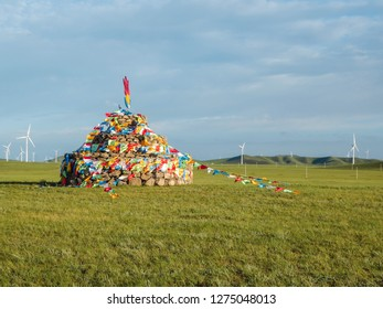 Aobao (Heaps of Stones) on the endless grassland of Inner Mongolia in China. In the background there are wind mills.