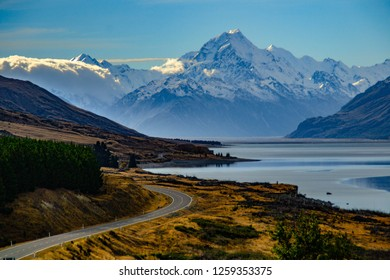 Aoraki/Mount Cook, road and turquoise lake Pukaki view from Peter´s Lookout, South Island, New Zealand. Warm colours, clear sky, snowy mountain tops. Iconic scenic New Zealand photo. Must visit place!