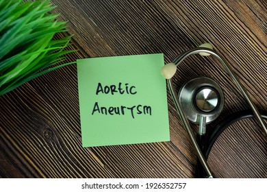 Aortic Aneurysm write on sticky notes isolated on Wooden Table.