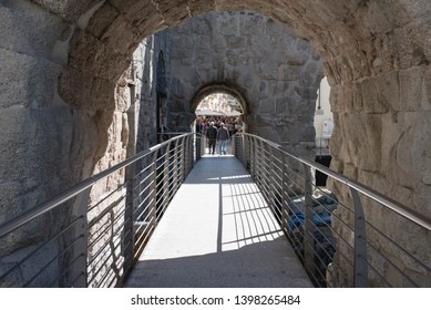 Aosta, Italy - May 10, 2019: two old men from behind walk through a stone arch of Porta Praetoria in Aosta, Italy