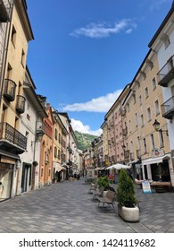 Aosta, Italy - May 2019. The morning light pours over the colorful buildings on the pretty quiet street in the Aosta valley