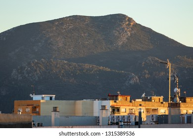 Apartament blocks in Spain during warm sunset with mountains in background