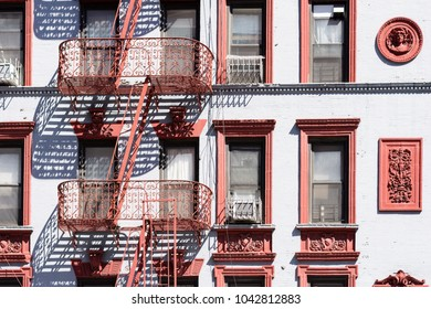 Apartament house building with outdoor staircase, iron balconies and red decoration on a facade, Manhattan, New York, USA