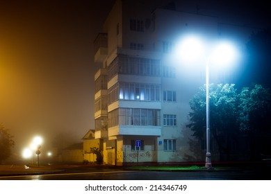 Apartment block on empty night city street covered with fog, blurred city lights glow through misty haze