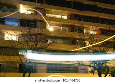 apartment building in the city with balconies and shooting lights at night