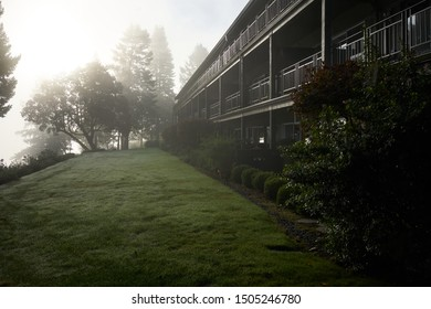 Apartment building exterior in a scenic natural setting on a foggy autumn morning.