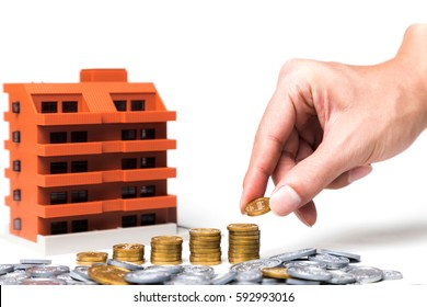 apartment building and funds, hand holding a coin