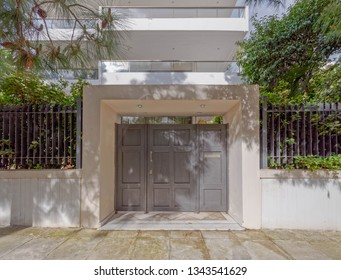 apartment building's facade and main entrance with grey painted metallic double doors