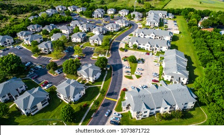 Apartment buildings and multistory townhomes a new development urban housing and Austin living - Aerial drone view - modern curved roads and large townhomes and square buildings