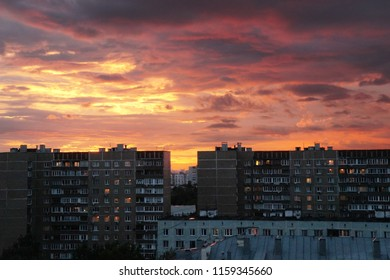 Apartment buildings and roof of school against the background of sundown sky.