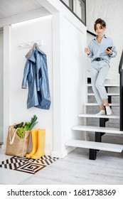 Apartment hallway with yellow rubber boots, outwear and shopping bag full of fresh food, motion blurred female figure walking the stairs