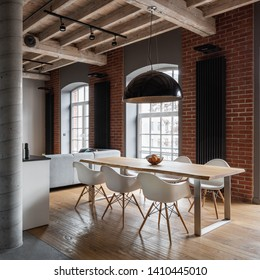 Apartment with industrial brick wall, wooden ceiling and dining table