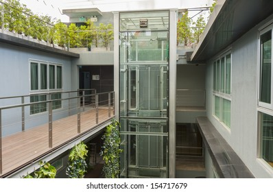 apartment interior with walkway bridge and glass lift.