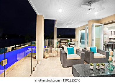 Apartment with kitchen wear and natural view, white candles also flower vases on the table, swimming pool in garden,evening time scene, sink attached to wall near gas cooker, perfect lightning.