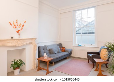 Apartment living room interior with vintage furniture, white walls, and a sealed fireplace